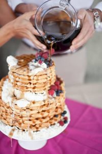 A couple pours syrup onto their waffle wedding cake.